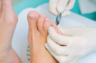 A podiatrist giving nail care to a client.